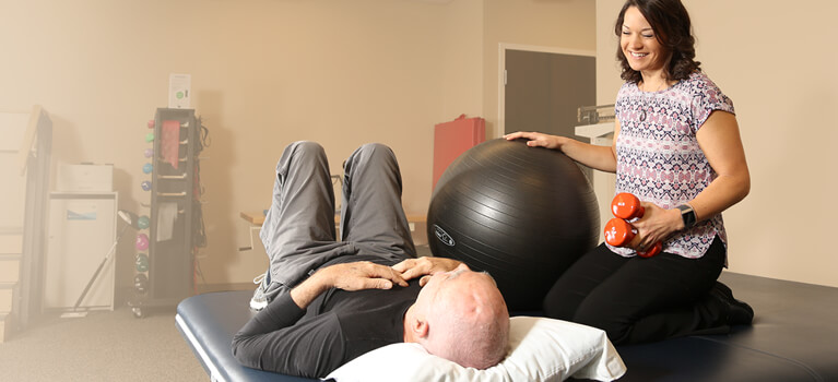 Physician helping patient - Our approach to physical therapy